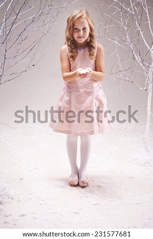 Adorable little girl in smart dress with heap of snowflakes on her palms looking at camera - stock photo