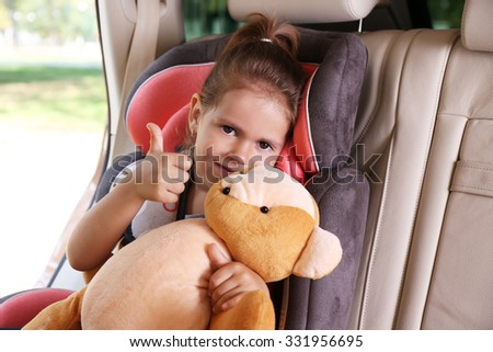 Adorable little girl in the car with teddy bear - stock photo