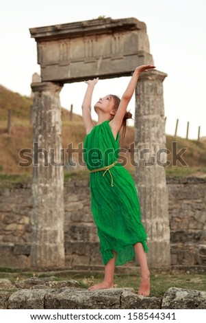 Adorable little girl in the emerald dress on a background of ancient sites of the ancient Greek city of Patikapey/Excavations on Mount Mithridates, the ruins of the ancient city of Pantikapaion, Kerch - stock photo