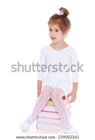 Adorable little girl is sitting on a big pile of books. Studio photo, isolated on white background. - stock photo