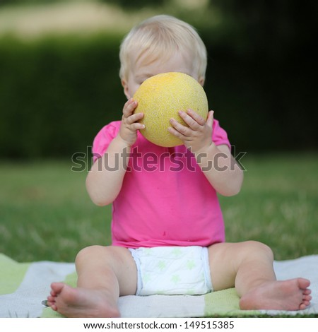 Adorable little girl is sitting on a carpet in a park and biting on a half of melon - stock photo