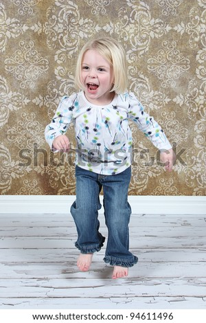 Adorable little girl jumping in air in studio