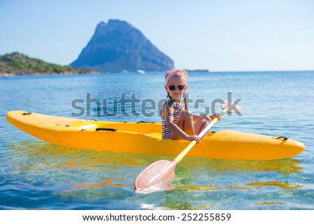 Adorable little girl kayaking during summer vacation
