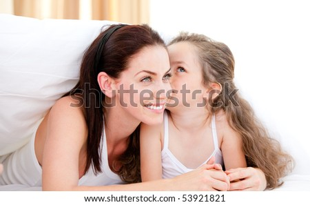 Adorable little girl kissing her mother lying on a bed - stock photo