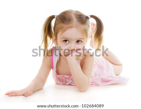 Adorable little girl laying on the floor and looking left on white background - stock photo