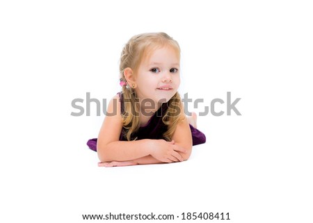 Adorable little girl laying on the floor and looking left on white background