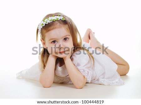 Adorable little girl laying on the floor isolated on white background - stock photo
