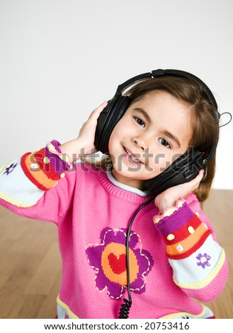 adorable little girl listening to music through headphones - stock photo
