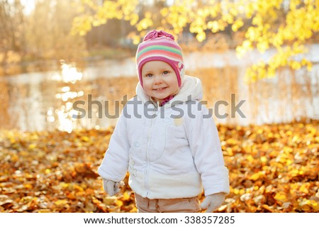 Adorable little girl little girl in a white jacket smiling amid Sunny autumn landscape - stock photo