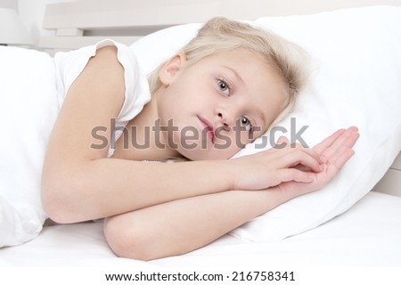 Adorable little girl looking at the camera  lying in bed  - stock photo