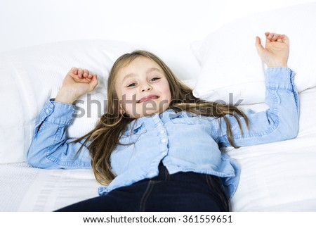 Adorable little girl looking at the camera on bed - stock photo