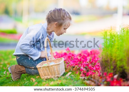 Adorable little girl looking for Easter eggs outdoors - stock photo