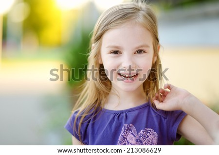 Adorable little girl lost her milk tooth - stock photo