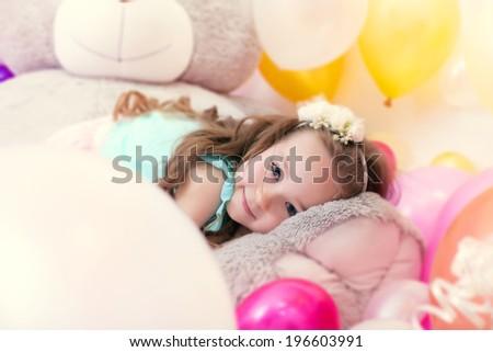 Adorable little girl lying on plush bear - stock photo