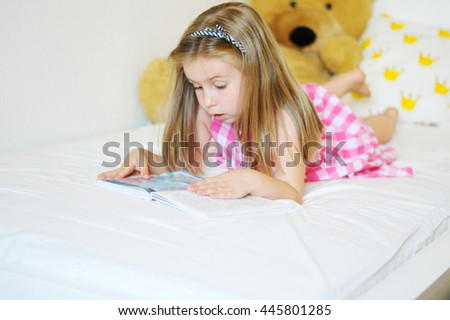 Adorable little girl lying on the bed and reading a book - stock photo