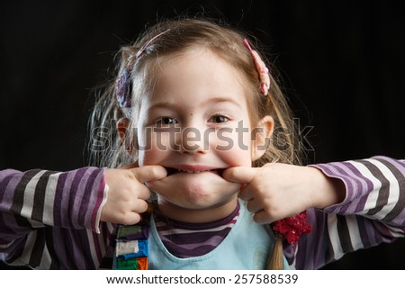 Adorable little girl making faces for the camera, black background - stock photo