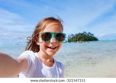 Adorable little girl making selfie in at tropical beach on Rarotonga island during summer vacation - stock photo