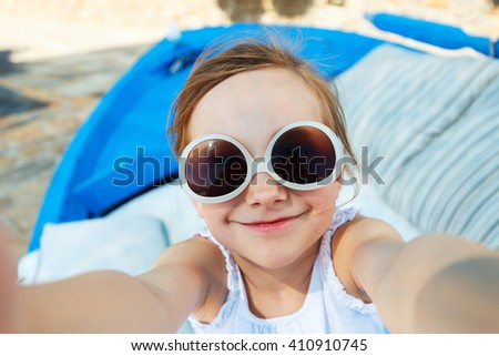 Adorable little girl making selfie with mobile phone outdoors on sunny summer day