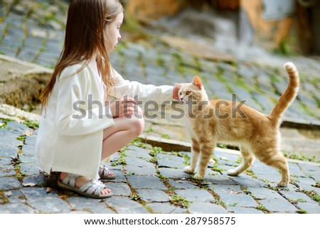 Adorable little girl met a cat while walking narrow streets ot typical italian town - stock photo