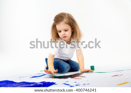 Adorable little girl, modern hair style, white shirt, blue jeans is drawing pictures by her hands with paints. Isolate. - stock photo