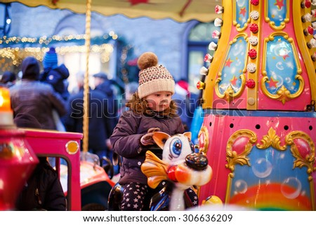 Adorable little girl on a carousel at Christmas funfair or market, outdoors. Happy child having fun. Traditional xmas market in Germany, Europe. Holiday, children, lifestyle concept. - stock photo