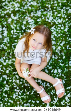 Adorable little girl on a grass covered with white flower petals on spring day - stock photo