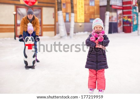 Adorable little girl on skating rink with father and cute sister in the background - stock photo