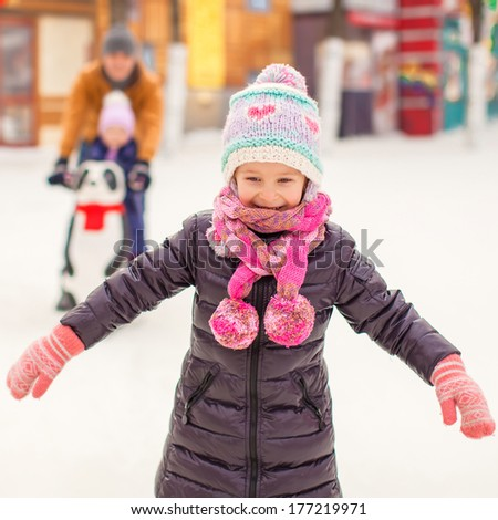 Adorable little girl on skating rink with father and sister - stock photo