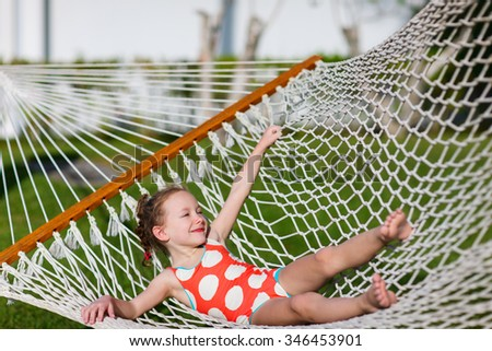 Adorable little girl on summer vacation relaxing in hammock - stock photo