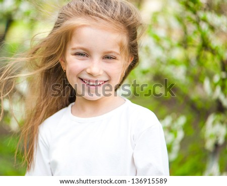 adorable little girl on the meadow in solar  day - stock photo