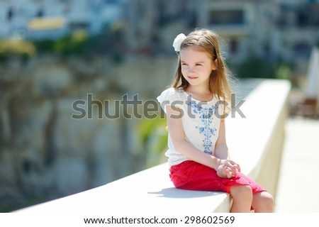 Adorable little girl on warm and sunny summer day in typical italian town - stock photo