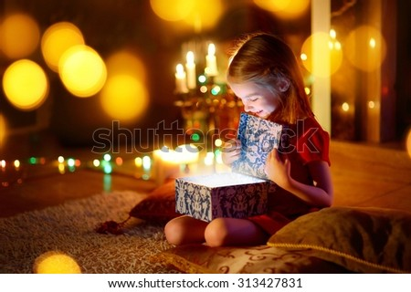 Adorable little girl opening a magical Christmas gift by a Christmas tree in cozy living room in winter