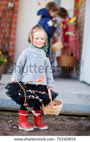 Adorable little girl outdoors collecting chocolate eggs as part of Easter tradition in Finland - stock photo