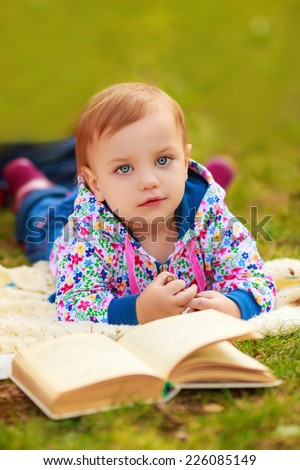 Adorable little girl outdoors. lie on the grass. read a book  - stock photo