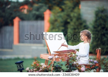 Adorable little girl painting a picture on an easel on a warm day outdoors - stock photo