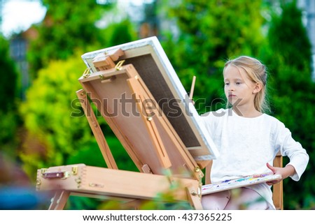 Adorable little girl painting a picture on easel outdoors - stock photo