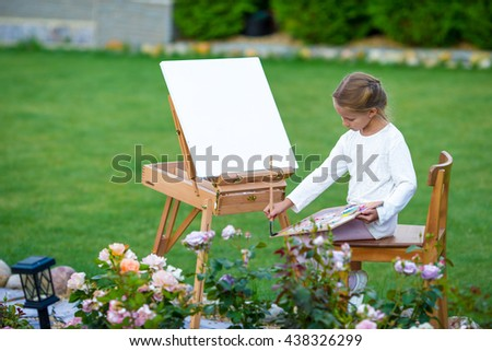 Adorable little girl painting a picture on easel outdoors. Little artist keen on her hobby. - stock photo