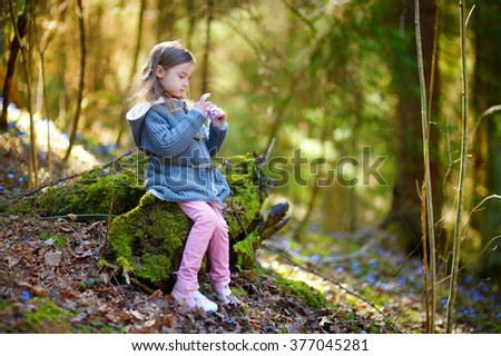Adorable little girl picking the first flowers of spring in the woods on beautiful sunny spring day - stock photo