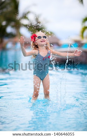 Adorable little girl playing at a swimming pool - stock photo