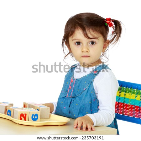 Adorable little girl playing at a table with dice. Montessori school .White background, isolated photo. - stock photo