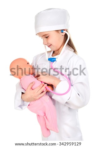 Adorable little girl playing at the doctor examining her doll on a white - stock photo