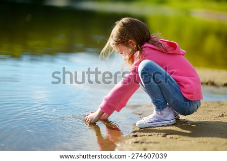 Adorable little girl playing by a river in autumn park on a beautiful sunny day - stock photo