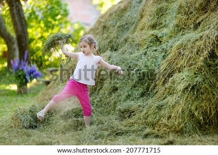 Adorable little girl playing in a haystack on beautiful summer day