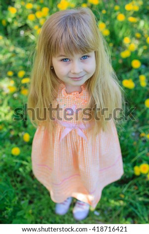 Adorable little girl playing in blossoming dandelion on spring day - stock photo