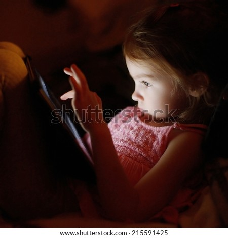 Adorable little girl playing on a digital tablet - stock photo