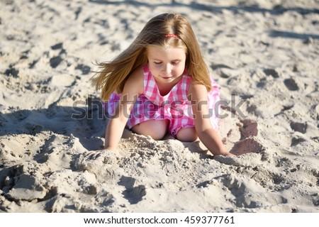 Adorable little girl playing on beach