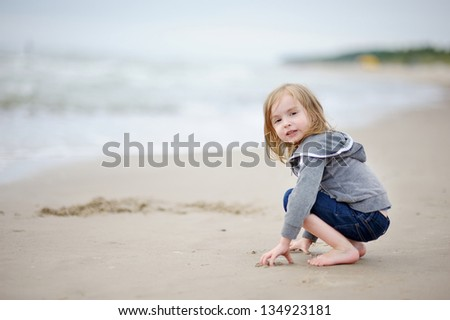 Adorable little girl playing on the beach - stock photo