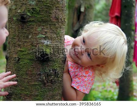Adorable little girl playing peekaboo  - stock photo
