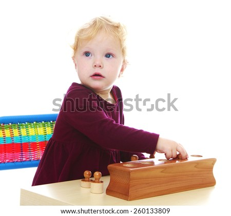 Adorable little girl playing while sitting at the table - isolated on white. - stock photo