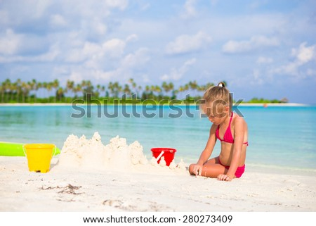 Adorable little girl playing with beach toys during tropical vacation